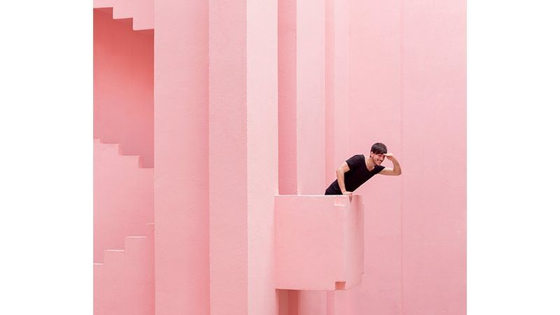 A man in black leans out of a pink balcony in an all-pink building stairwell. Photo by Daniel Rueda and Anna Devís.